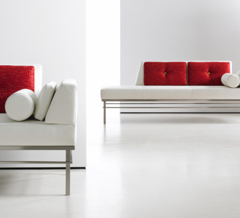 white modern low bench on chrome frame with red pillows